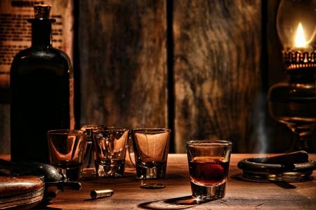 whisky: American West légende whisky coup boisson en verre avec des verres vides et une bouteille de whisky vintage sur un comptoir de bar en bois antique avec le cowboy pistolet revolver dans une scène de saloon frontière antique éclairée par la lampe à huile sombre