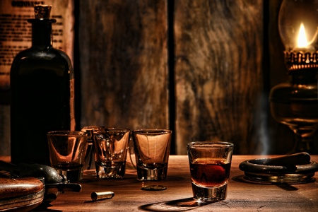 whiskey: Amerikaanse Westen legende whiskey shot glas drinken met lege glazen en vintage whisky fles op een antieke houten bar met cowboy revolver pistool in een antieke grens saloon scene verlicht door dim olielamp