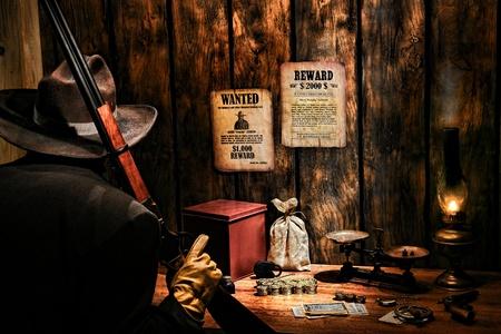 monedas antiguas: American West Leyenda guardia de seguridad armado con el rifle y sombrero de vaquero guarda una nómina ferrocarril occidental y la oficina de ingresos con monedas de oro y dinero de la vendimia con una caja fuerte y una bolsa valiosa sobre un viejo escritorio pagador
