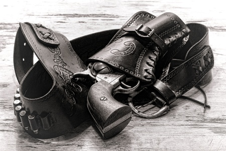 American West legend revolver style old six-shooter gun in antique cowboy leather holster on grunge aged wood planks photo