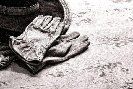 ranching: American West rodeo lleva guantes de cr�a de cuero aut�ntico sombrero de vaquero del oeste sobre una cosecha lazo lazo m�s grunge tablones de madera tabla granero rancho