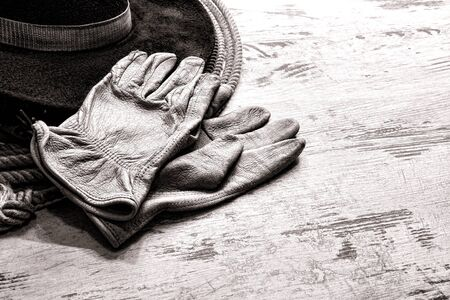 ranching: American West rodeo worn leather ranching gloves on authentic western cowboy hat atop a vintage lasso lariat over grunge wood planks ranch barn table