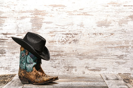American West rodeo black cowboy hat atop pair of designer fashion leather cowgirl boots with fancy decorative stitching and cutouts on weathered grunge wood ranch barn background Stock Photo