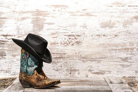 Amerikaanse Westen rodeo zwarte cowboy hoed bovenop paar designer fashion lederen cowgirl laarzen met mooie sierstiksels en uitsnijdingen op verweerde grunge houten boerderij schuur achtergrond