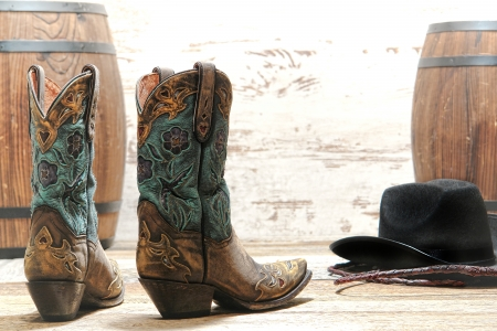 legends folklore: American West rodeo cowgirl designer leather boots with fancy decorative stitching and cutouts with black cowboy hat at an old style barrel racing event