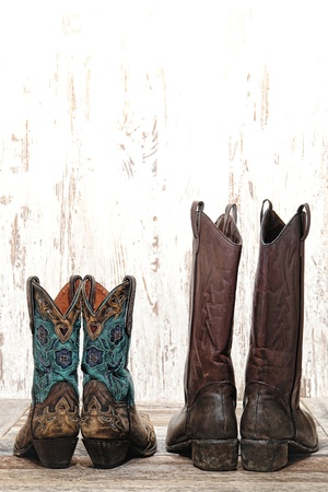 American West rodeo pair of cowgirl and cowboy leather boots as couple on old wood planks  Stock Photo