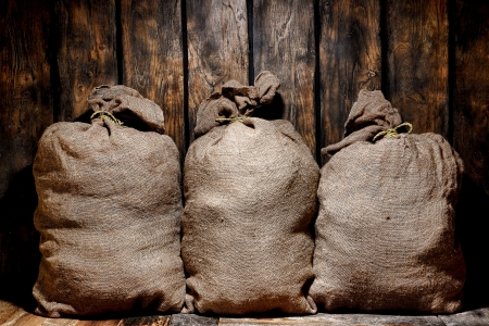 burlap sac: Three vintage brown burlap sac bags filled with dry goods ready for cargo shipment in an old antique provision storage and shipping warehouse keep with wood barn plank walls  Stock Photo