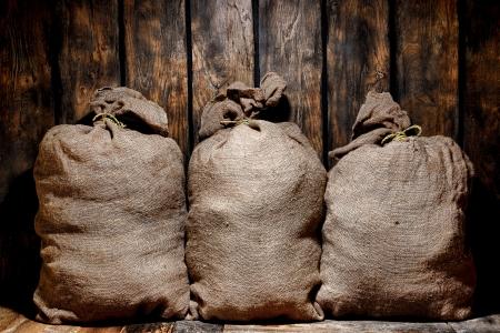 abastecimiento: Tres antiguos marr�n saco de arpillera bolsas llenas de productos secos listos para el env�o de carga en un viejo anticuario aprovisionar almacenamiento y almac�n de env�o seguir con paredes de tablones de madera del granero