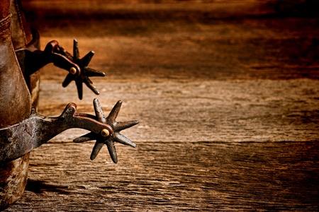 ranching: American West rodeo vendimia montar con espuelas afiladas p�as rowel en aut�nticas botas de vaquero de cuero tradicionales occidentales en viejo fondo de madera envejecida en un antiguo granero de la ganader�a Foto de archivo