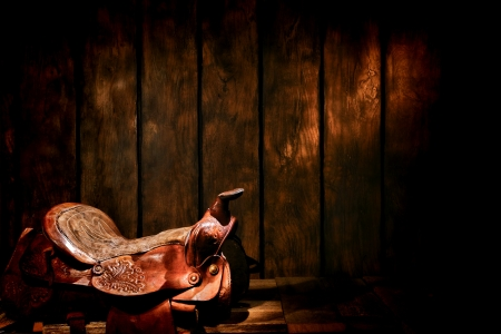 American West legend traditional rodeo cowboy authentic worn and used brown leather western saddle in an old weathered ranch wood barn