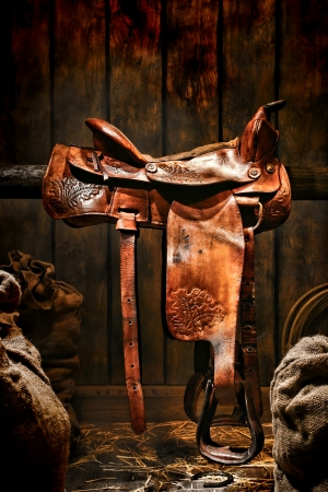 legends folklore: American West legend authentic rodeo cowboy used and worn brown leather western saddle on a wood beam in an old ranch wood barn Stock Photo