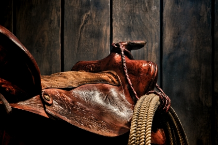American West Legend rodeo cowboy roping lariat lasso hanging on an authentic used and worn brown leather western saddle in an old ranch barn