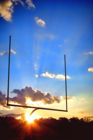 장엄한 일몰 동안 극적인 푸른 하늘 엔드 존에있는 미식 축구 스포츠 경기장의 목표는 게시물