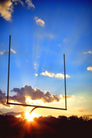 American football sport stadium goal posts in end zone over dramatic blue sky during a spectacular sunset photo