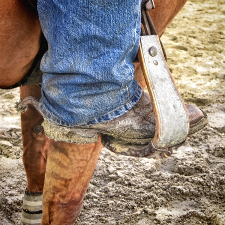 caked: American West rodeo dirty traditional leather boot caked with mud and dirt with western spur on a riding stirrup on a horse  Stock Photo