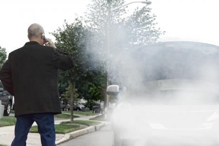 Gestrande automobilist bestuurder gestrand op de kant van de weg te bellen op mobiele telefoon voor noodhulp hulp in de buurt van kapotte auto met rook van vuur of stoom uit de slang lek roken uit open auto motorruimte