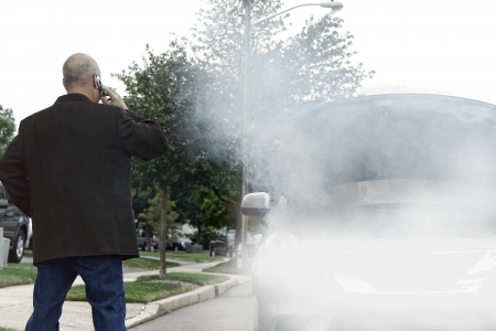 Stranded motorist driver stranded on the side of the road calling on cell phone for emergency assistance help near broken down car with smoke from fire or steam from hose leak smoking out of open automobile engine compartment