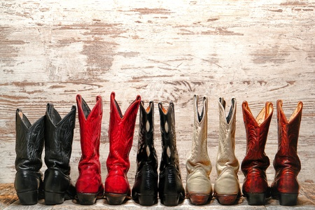 botas vaqueras: American West Leyenda vaquera botas de cuero del tal�n vista trasera en l�nea recta sobre el oeste viejos tablones de madera en una sala de baile de pa�s Foto de archivo