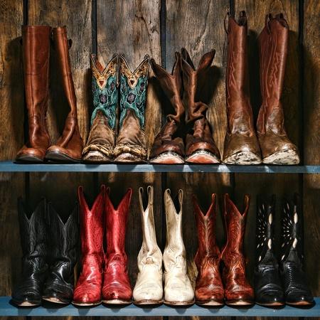 country: Amerikaanse Westen rodeo gebruikte en versleten cowboy en cowgirl leren laarzen collectie gestapeld op oude houten plank in een ranch schuur