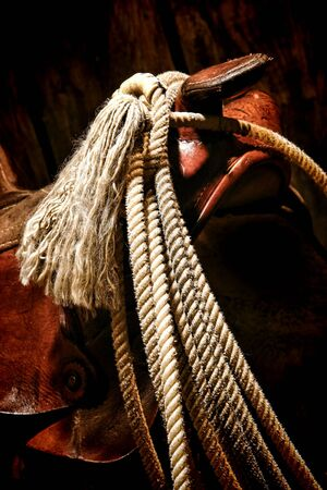 American West rodeo roping lasso lariat rope with tassel hanging on an old western cowboy saddle horn and swell