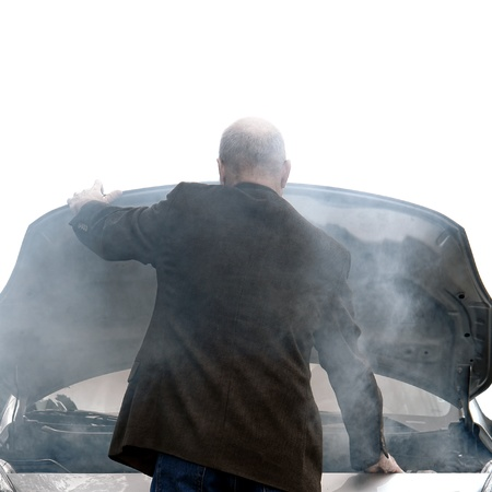 Auto driver standing in front of a broken down car open engine compartment hood with smoke from an automotive fire or hose leak steam waiting for emergency repair on a road