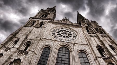 rite: Allegoric and dramatic wide view of the Cathedral of Our Lady of Chartres gothic style Roman catholic rite church with stormy sky in France