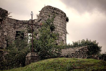 Oud ijzer Christelijke kruis staande op een stenen sokkel in de ruïnes van een middeleeuws kasteel fort bedekt met begroeide vegetatie in Frankrijk Stockfoto