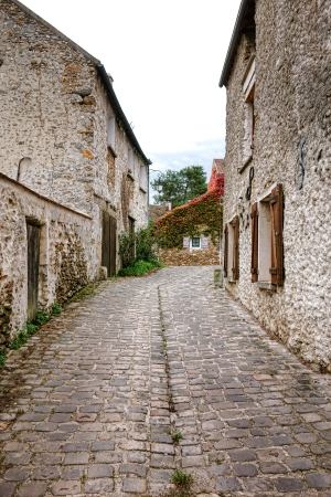 timeless: Old and narrow cobblestone street with antique stone masonry traditional farm houses in a rural French village in timeless France Stock Photo