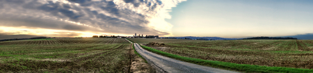 Sunset with spectacular evening dusk sky over a small rural village with church and open field and road farmland of the scenic Vexin region in France in wide panoramic landscape view photo