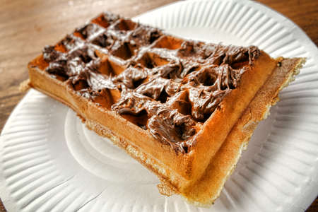 smeared: Hazelnut and chocolate sweet dessert and breakfast spread paste smeared on a fresh baked warm waffle as a French and European traditional favorite snack treat