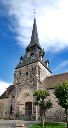 steeples: Traditional stone gothic church place of worship building with unusual multiple dormers on steeple covered with shingles in a small rural village in France Stock Photo
