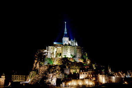 michel: Mont Saint Michel Abbey monastery and fortifications on its famous landmark island rock lit with lights at night in the French province of Normandy in Northwestern France Stock Photo