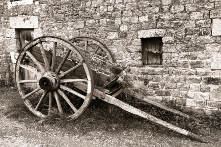 old wood farm wagon: Antique farm carriage transportation cart with wood wagon wheel in front of an old farm wall in rural France