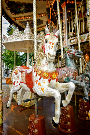carousel horse: Vintage carved wood nostalgic carousel riding horse with antique painted decor mounted on a classic brass pole on an old amusement merry go round Stock Photo