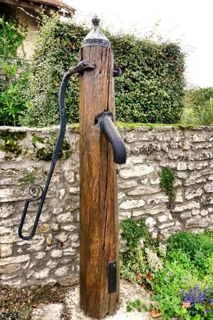 hand crank: La madera vieja mensaje p�blico de agua de bombeo de fuente con metal fundido hierro de la bomba de la manivela y la espita del grifo cerca de una pared de piedra antigua en una peque�a plaza del pueblo franc�s en la Francia rural Foto de archivo