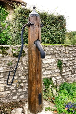 hand crank: Old wood post public water pumping fountain with cast iron metal hand crank pump and faucet spigot near an antique stone wall on a small French village square in rural France  Stock Photo