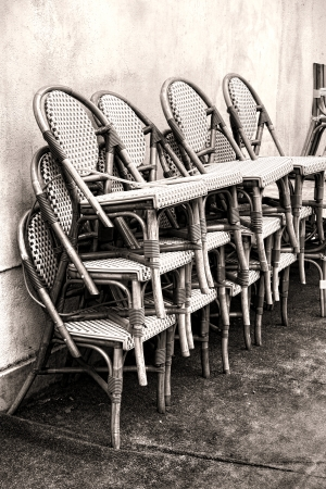french cafe: Classic bamboo wicker cafe seating chairs with plastic weave cushions stacked against an old wall outside a French bistro in a small town in France Stock Photo