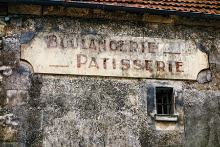 bakery store: Boulangerie and patisserie French antique bakery and pastry shop old and distressed store sign hanging on a derelict grunge wall of an ancient and damaged building in a small rural town in France Stock Photo
