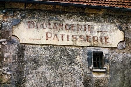 patisserie: Boulangerie e patisserie francese panificio antichi e pasticceria vecchio e afflitto negozio segno appesa su una parete grunge derelitto di un antico edificio e danneggiato in un piccolo paese rurale in Francia