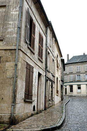 grates: Old masonry buildings and aged antique row houses on quaint ancient cobblestone paved street in a small French town in a rural province of France (all modern objects such as signs, wires, antennas and sewer grates have been removed)