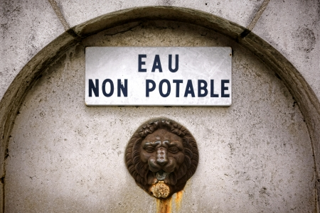 potable: Non drinkable water enamel warning sign in French over antique lion head spout on an old public square fountain in France Stock Photo