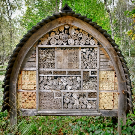 Bee and useful garden insect housing and nesting house box made of wood and natural components to attract beneficial organic cultivation bugs  Stock Photo