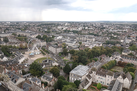 Aerial cityscape view from above of provincial French city of Chartres in the Beauce region of France with Ferris wheel and train station among urban streets with trees in parks and old town buildings below photo