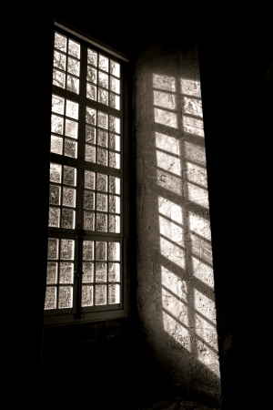 shadow: Bright sunlight filtering through the old leaded glass of an antique wood window and drawing a shadow pattern of muntin and mullion unto an ancient interior wall inside a historic buidling