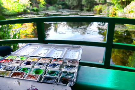 monet: Open box of used assorted watercolor artist paint in water based color cakes pan set left on a bridge in the water lily garden of famous French impressionist painter Monet in Giverny  Stock Photo