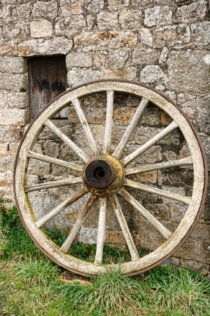 old wood farm wagon: Antique and weathered wood cart wagon wheel with vintage wooden spokes leaning against an old stone farm building wall