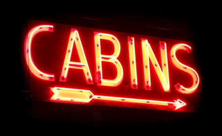 Old vacation camp cabins rental place vintage neon sign with direction arrow glowing in the dark with diffused red glow Stock Photo - 23907658
