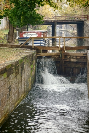 rushing water: Chesapeake and Ohio Canal old lock gates with rushing water pouring and historic replica travel barge excursion boat in the romantic Georgetown neighborhood of Washington DC