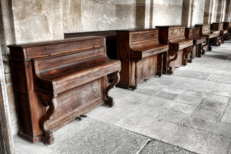 upright: Row of vintage upright study pianos with weathered wood cabinet in an old music school lesson hall with antique stone walls and floors