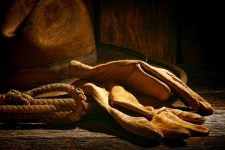 ranching: American West rodeo tough leather ranching gloves on authentic lasso lariat with vintage western cowboy hat in on old ranch barn weathered wood table